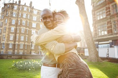 Young black tousits couple passionately hugging in a park, laughing and having fun.