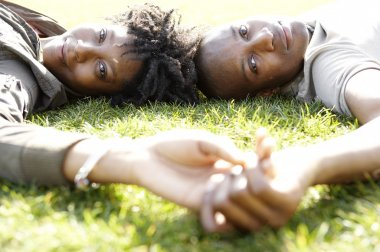 Close up portrait of a young african american couple laying down on green grass in the city