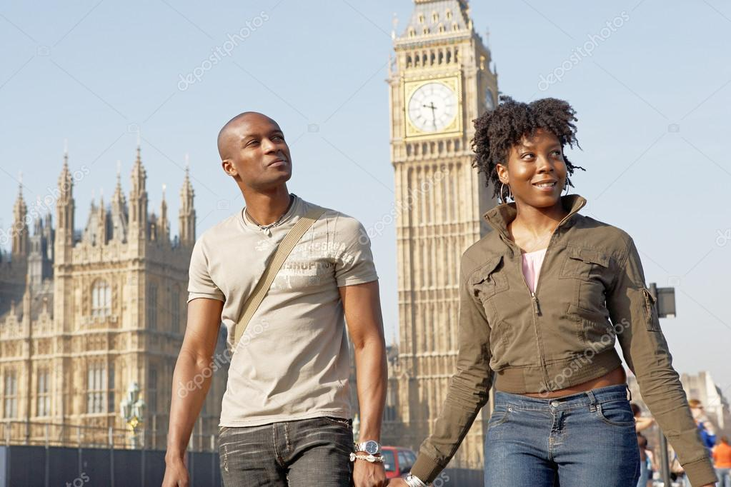 attractive black tourist couple holding hands and walking
