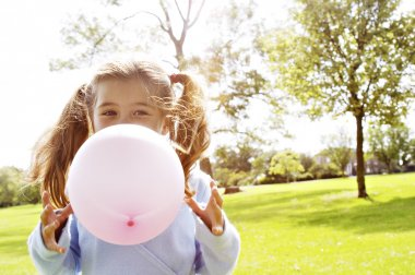 Young girl blowing a pink balloon in the park on a sunny day.