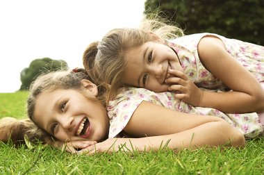 Two sisters laughing and playing in the park