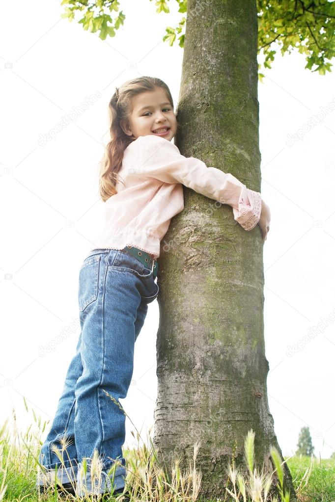 Young girl in the park hugging a tree on a hill, against the sky, and smiling to camera.