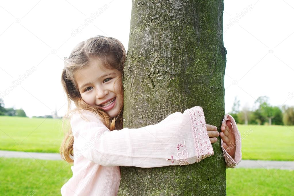 Smiling young girl hugging a tree in the park.