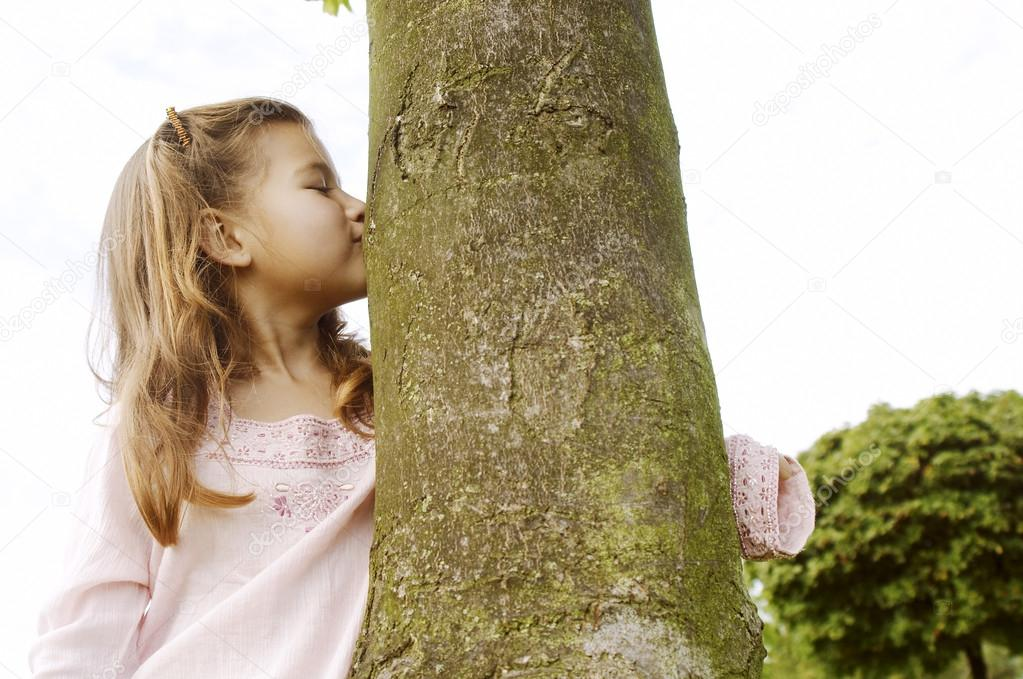 Young girl kissing a tree trunk in the park.