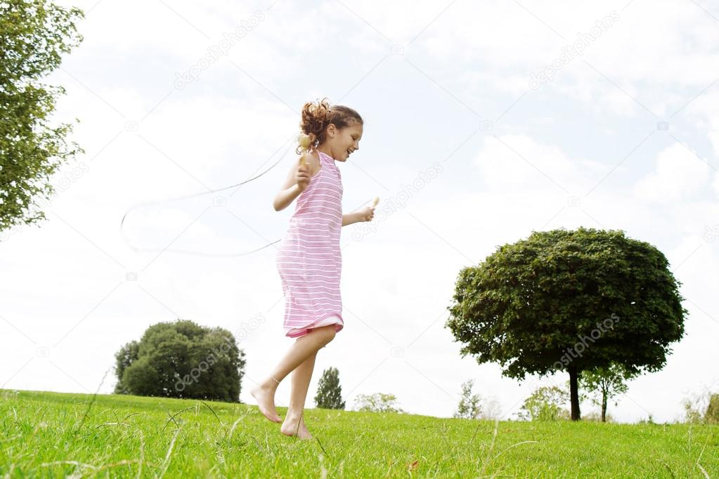 Profile view of a young girl playing skipping rope in the park, smiling.