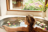 Photo Back view of a young woman bathing in a health spas flower bath.