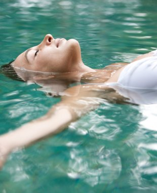 attractive young woman floating on a spa's swimming pool