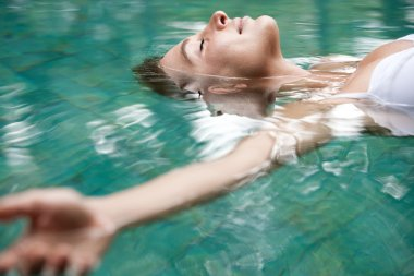 attractive young woman floating on a spa's swimming pool.