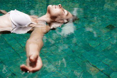 young woman floating in water while in a swimming pool on vacation.