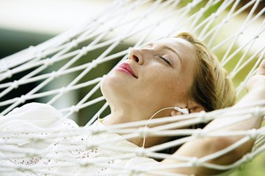 Close up portrait of an attractive blonde woman laying down on a hammock listening to music, with her eyes closed and smiling. stock vector