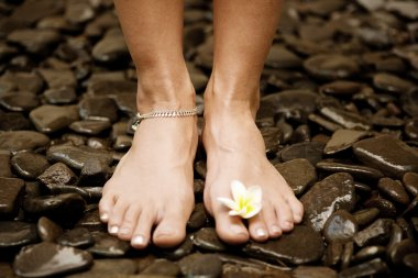 Young woman's feet standing on black natural stones