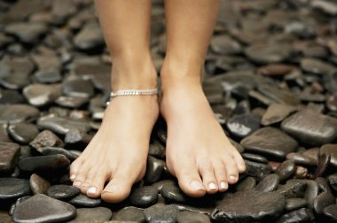 woman's feet wearing an anklelet and standing on black stones.