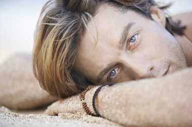 attractive young man laying down on a white sand beach.