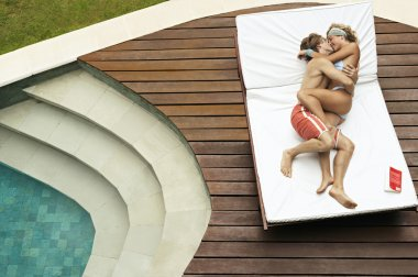 young couple playfully hugging and kissing on a sun lounger by the swimming pool.