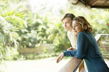 young couple on vacations, leaning on a balcony's veranda