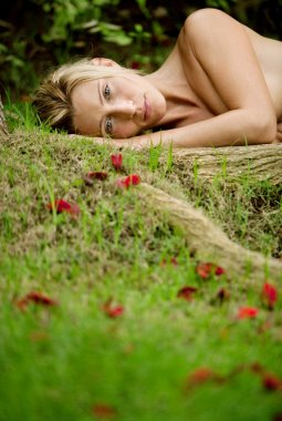beautiful blonde woman laying naked on green grass and tree roots