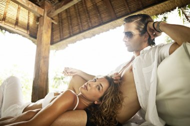 Sexy young couple lounging on an outdoors bed in a tropical hotel.