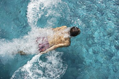 Over head view of a man diving into a swimming pool, splashing into the water.