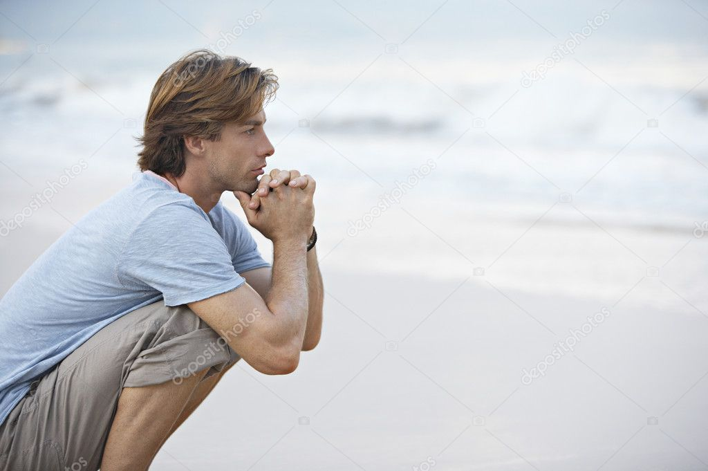 Young man crouching by the sea shore looking at sea