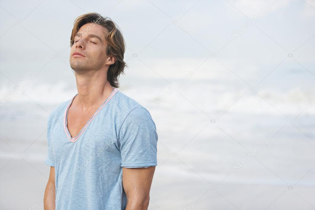 attractive man breathing fresh air while on the beach