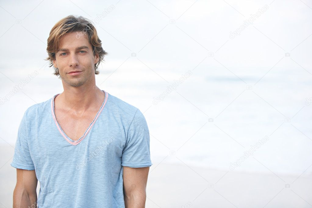 young attractive man on the beach with the sea in the background