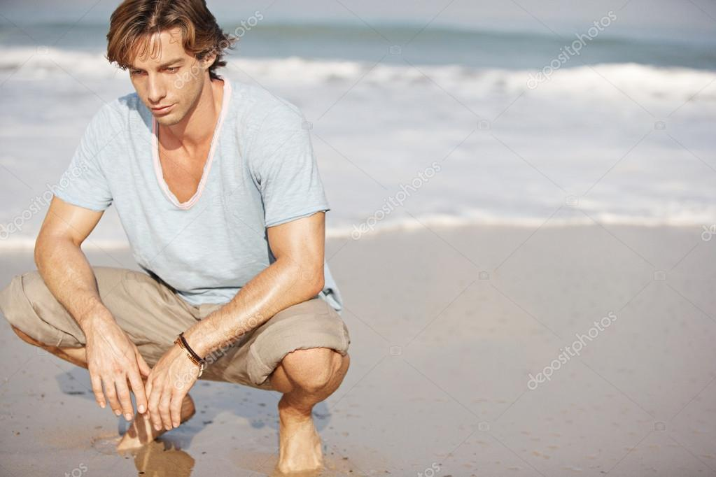 Young attractive man crouching by sea shore on a sunny day.