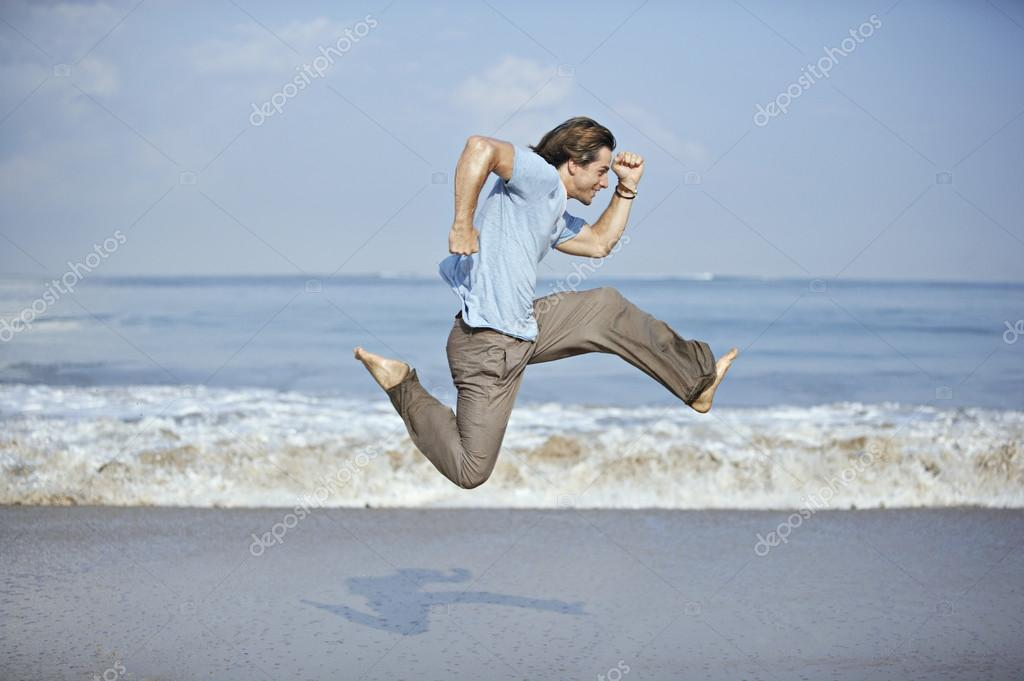 Attractive young man jumping with open legs by the sea shore.