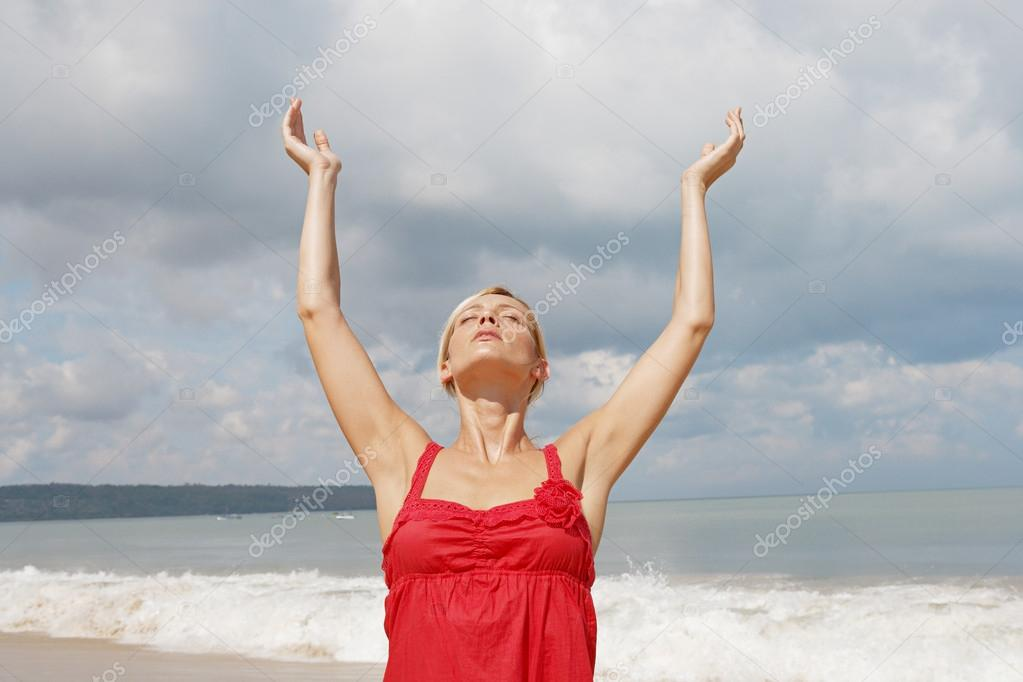 Attractive young woman stretching her arms up wile standing on a golden sand beach.