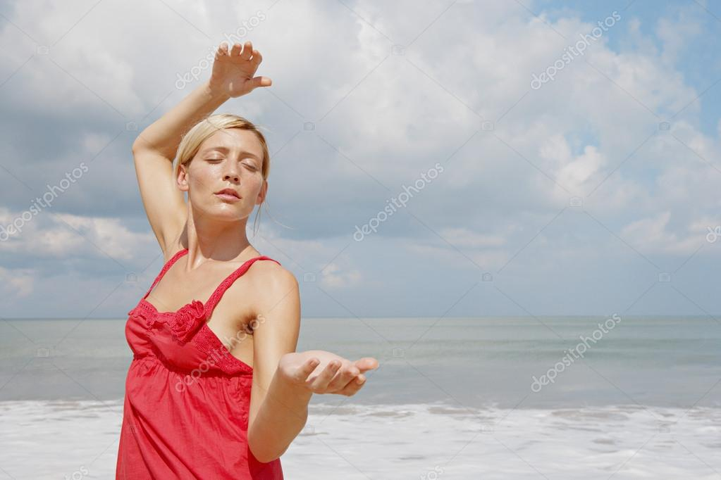Young attractive woman practicing martial arts on a beach.