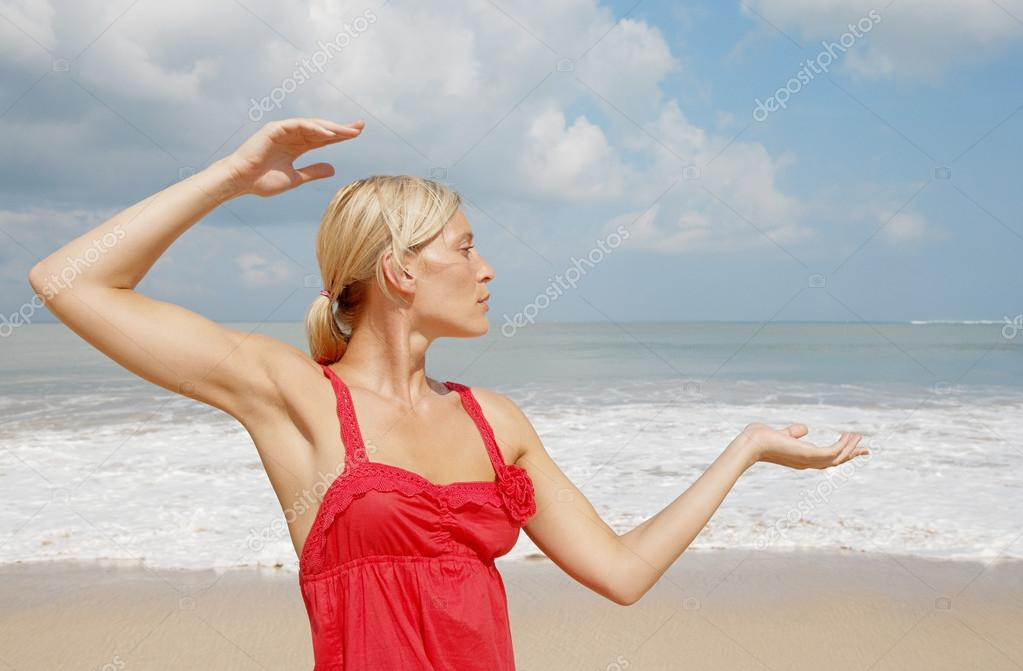 Young attractive woman practicing yoga on a beach.