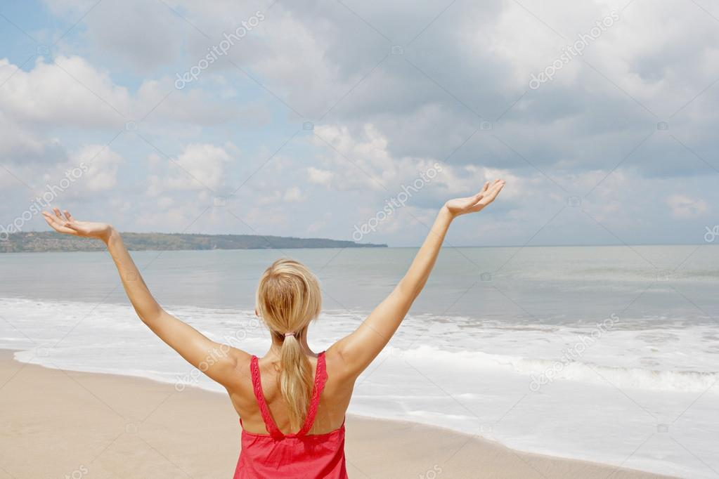 young woman with her arms outstretched in the air while standing by the shore