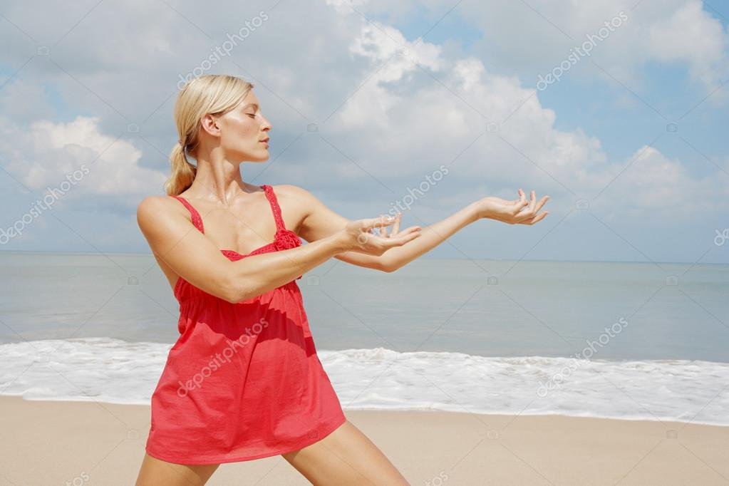 Portrait of an attractive woman practicing martial arts on the beach.