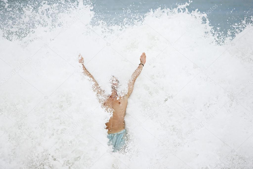 Large wave crashing on man's body while jumping in the sea