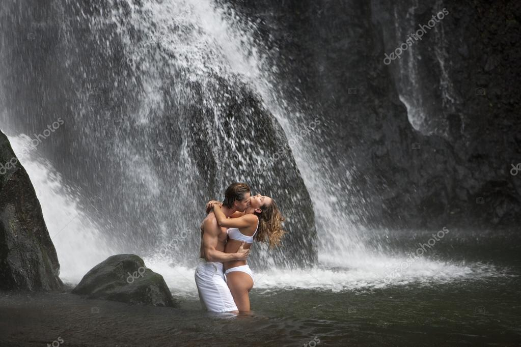 Couple hugging and kissing under waterfalls.