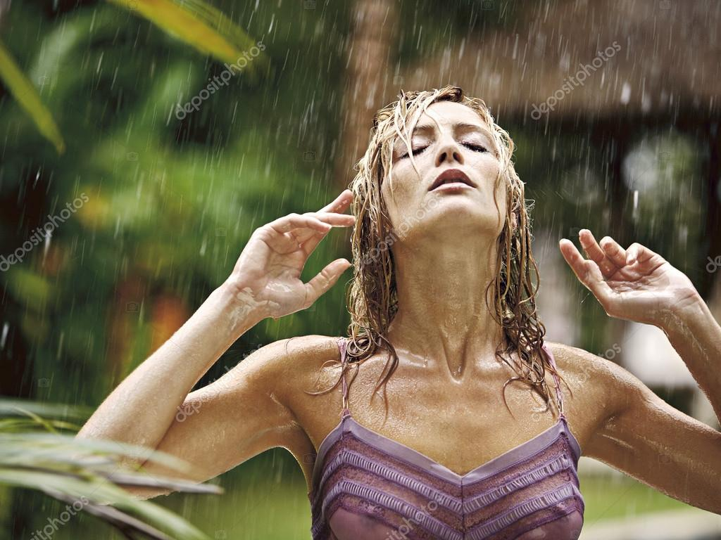 attractive young woman under the tropical rain