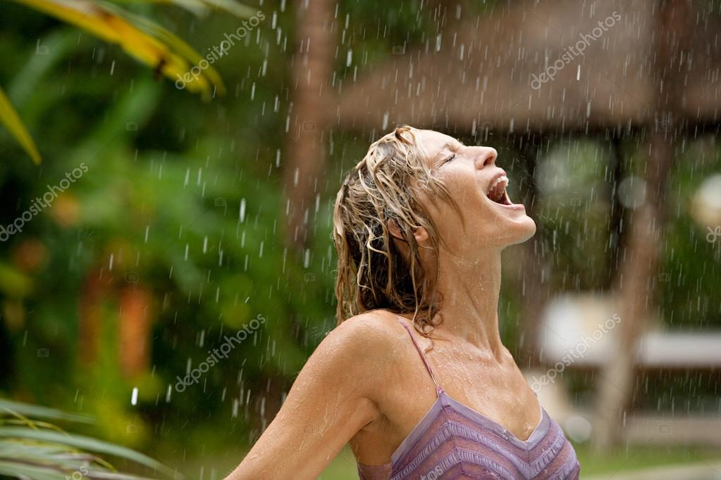 Profile of a young attractive woman under tropical rain with her mouth open.