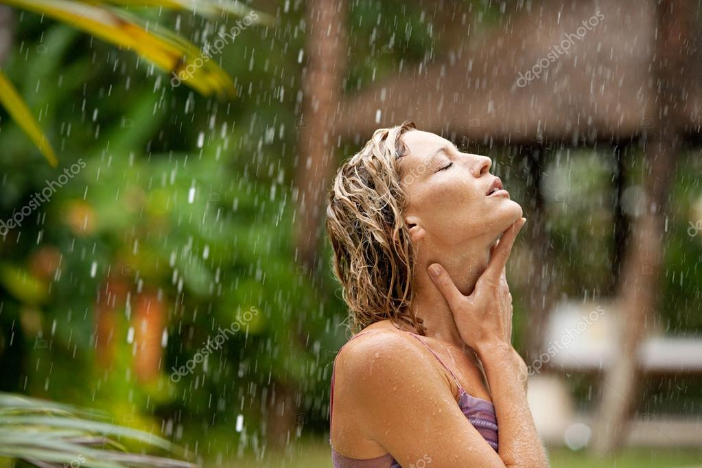 Attractive woman under tropical rain in an exotic garden.