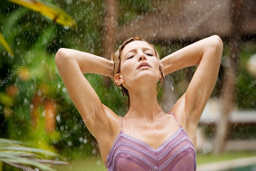 Portrait of a beautiful woman enjoying tropical rain falling on her in an exotic garden.