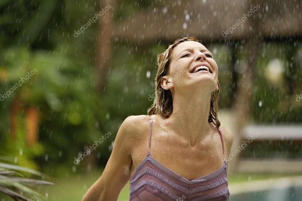 Attractive young woman on holiday under tropical rain, enjoying the shower.