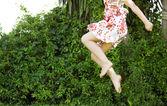 Fotografie Körperteil eines jungen Mädchens, das in einem grünen Gartenbereich in die Luft springt.