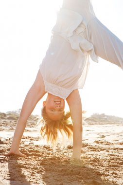 young girl doing cartwheels on a golden sand beach with the sun rays filtering through her body during sunset.