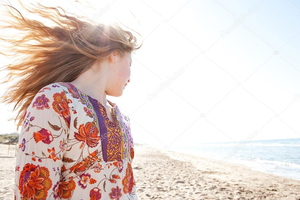 Young girl flicking her hair on a golden sand beach with the sun rays filtering through her hair while she smiles