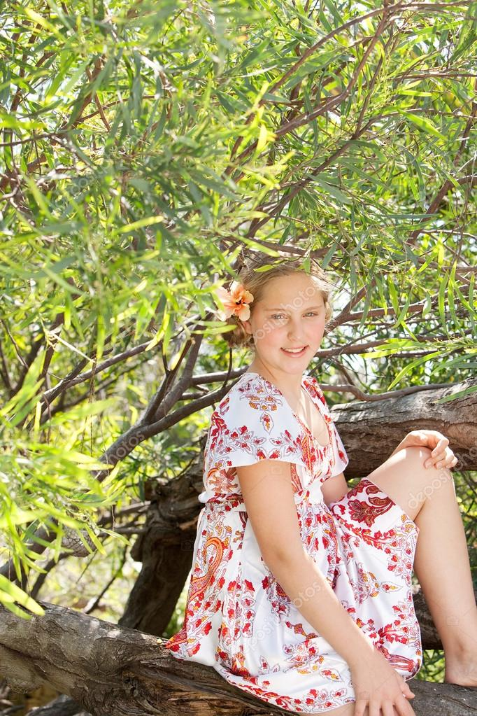 Young blond teenager sitting on a tree trunk while wearing a floral dress, smiling at camera.