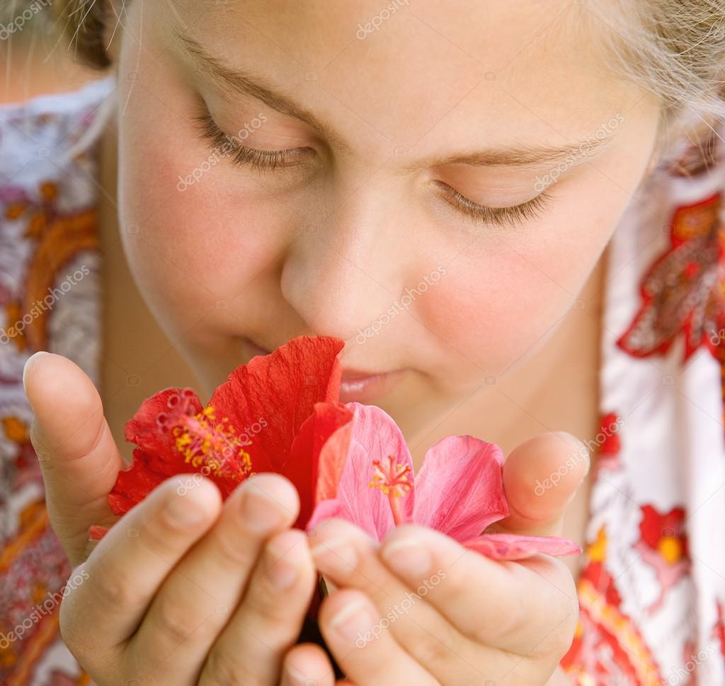plan le portrait d'une adolescente à l'odeur des fleurs d'hibiscus