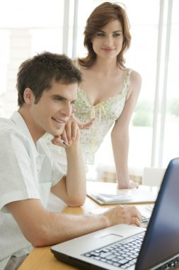 Man and woman working on finances at home.