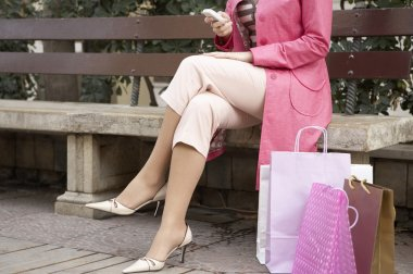 Sophisticated woman using a cell phone while sitting down with shopping bags.