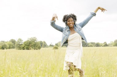 Young black woman dancing in a long grass field while listening to music