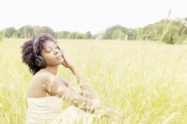 Attractive black woman sitting down in a long grass field