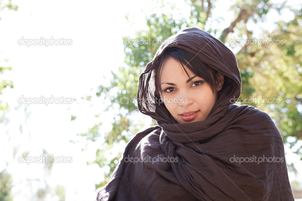 547901038c3 Portrait d une jeune femme musulmane portant un foulard sur la tête brun et  souriant à la caméra à l extérieur — Image de mjth