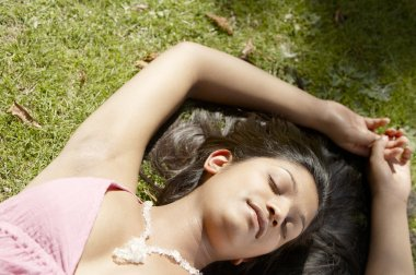 Over head portrait of a indian girl laying down on green grass in the park
